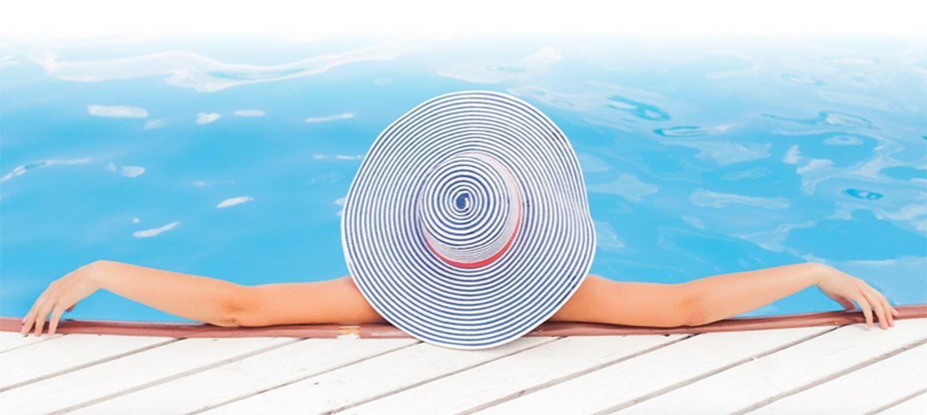 Chica con sombrero en piscina